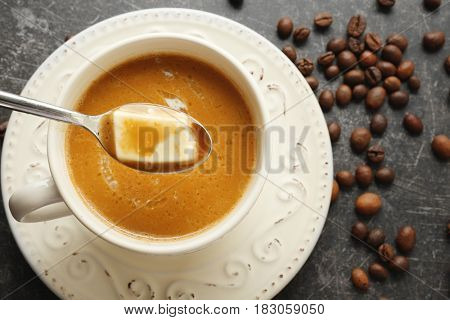 Cup of tasty butter coffee and spoon on grey background