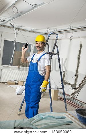 Construction Worker with Cellular Phone on Hand
