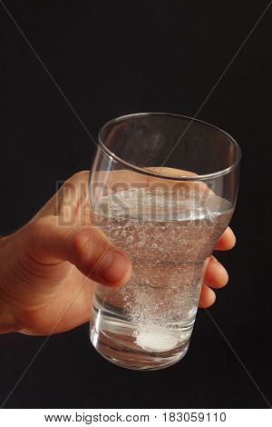 Hand with a glass of water and effervescent tablet on a dark background.