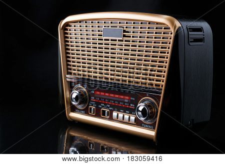 modern retro styled radio with audio player on reflective surface and black background