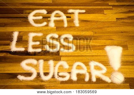 Eat less sugar sign with wooden background
