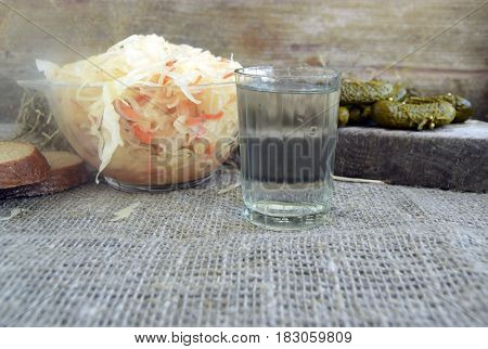 Cabbage fermented pickles and vodka are on a table. Traditional national Russian drink and snack.