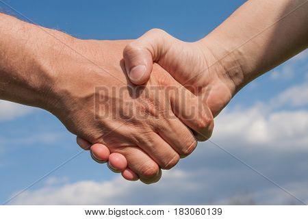 Man's handshake against a blue cloudy sky.