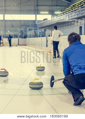 Playing a game of curling. Favorite winter game on ice.