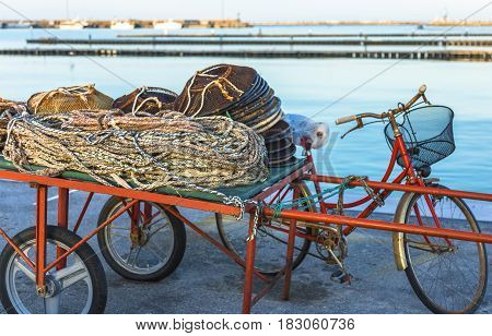 Old cart for carrying fishing ropes and fishing pots near a red bicycle