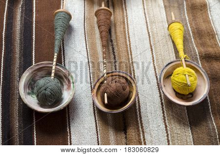 Threads made of alpaca's wool on wooden spindles