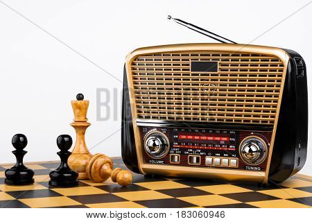 modern retro styled radio receiver with chess pieces on chessboard and white background