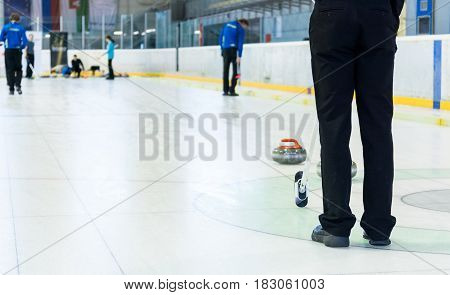 Playing a game of curling. Indoor sport played on ice.