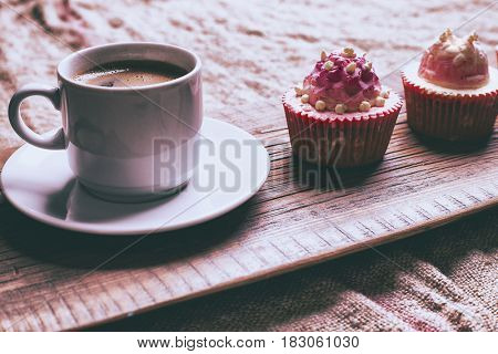 Cupcake and coffee on old dark rustic wooden table, selective focus, close-up