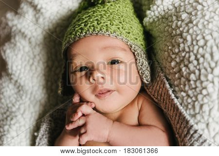 A newborn baby in a hat lies in a crib. The child falls asleep in the cradle