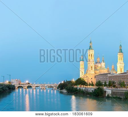 Panorama of Our Lady of the Pillar Basilica with Ebro River at dusk Zaragoza, Spain