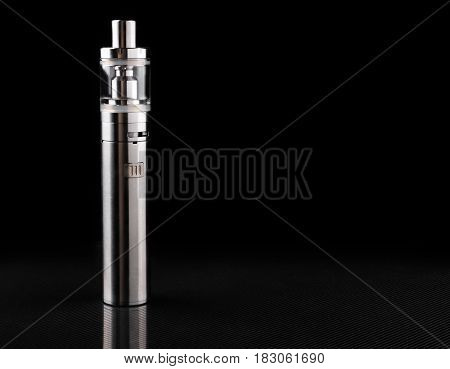 metallic electronic cigarette or vaping device on black background