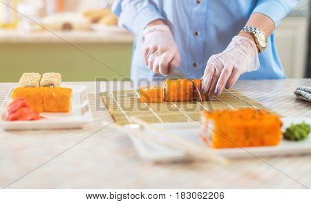 Cropped image of woman in gloves cutting sushi rolls on bamboo mat and serving on plates.