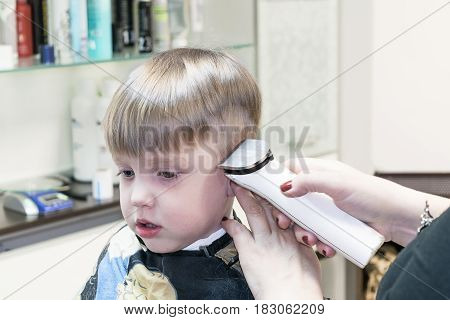 Little cute boy sitting in the chair at the hair salon. Covered with a cloak. It cut Barber electric hair clippers white. In the background are accessories.