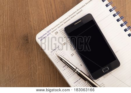 Mobile phone pen and agenda on a wooden background