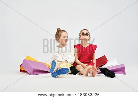 Pretty girls are sitting on the floor at the studio and aping. There are a mess around them of shopping bags. Shopping, purchases, buy, sale concept