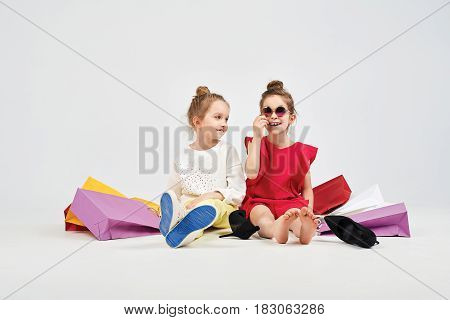 Little girls are sitting around shoppers bags and laughing with themselves. Next to them are oversized shoes. Shopping, purchases, buy concept
