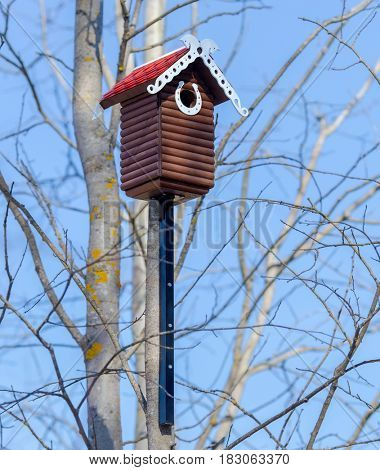 Nesting box. Carved wooden nest box handmade with red tile roof . Wooden house for birds on the tree.