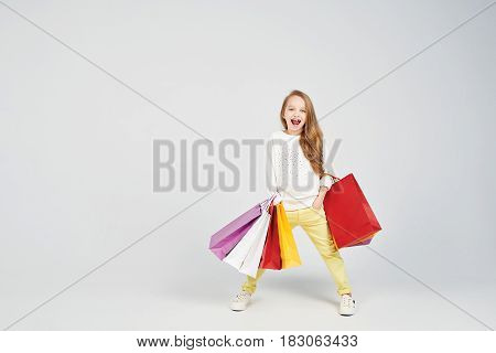 Blonde girl with a big smile is laughing at the camera. She is holding her hand in the pockets, and having lots of shoppers bags