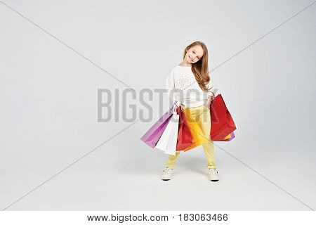Blonde girl is holding her hands in the pockets. She is smiling at the camera. Young lady has a lot of shoppers bags. Shopping, purchases, buy, sale concept