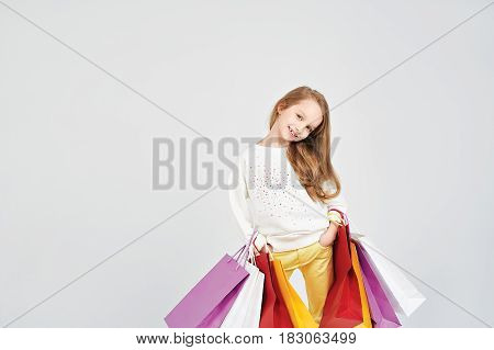 Smiling girls is having lots of colorful bags. Young lady is smiling to the camera. Shopping, purchases, buy, sale concept