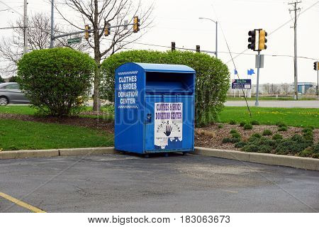 BOLINGBROOK, ILLINOIS / UNITED STATES - APRIL 14, 2017: Helping Hands provides a blue donation bin, for clothing and shoes, in the corner of the parking lot in the Concord Plaza in Bolingbrook.