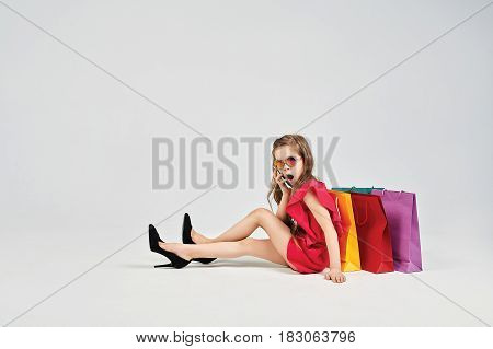 Little girl is wearing red outfit and oversized shoes. Young lady is talking to mobile phone. She is surprised and sitting around shoppers bags. Shopping, purchases, buy, sale concept
