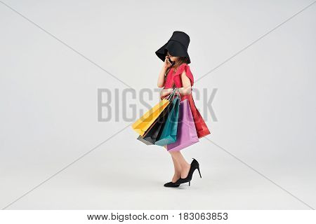 Young girl with shoppers bags is talking to the phone. Little girl is wearing oversized shoes and hat and looks like business woman. Shopping, purchases, buy, sale concept
