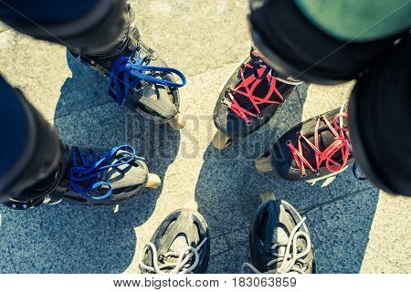 Top view of feet of roller skaters wearing freeskate inline skates standing close to each other. Extreme sports and friendship concept.