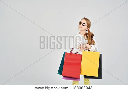 Pretty girl is wearing sunglasses. She is holding lots of colorful shoppers bags. Shopping, purchases, buy, sale concept