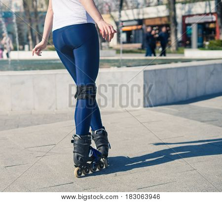 young Roller Girl is learning how to skate. First time on roller skates. View from back