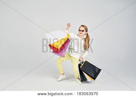 Little girl in sunglasses is posing at the camera. Young lady has a lot of shoppers bags. Shopping, purchases, buy, sale concept
