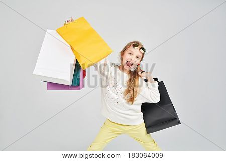 Laughing girl is holding lots of colorful bags. Shopping, purchases, buy, sale concept