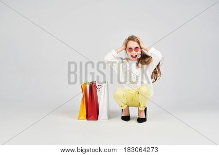 Young gil is sitting on the floor and holding her head. Little girl is shocked. There shoppers bags near her.Shopping, purchases, buy, sale concept