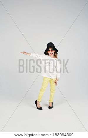Little girl in a oversized hat and shoes is posing to camera. She is showing something by her hand.
