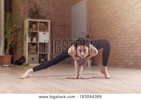Young slim woman standing on tiptoe doing stretching exercise bending forward facedown indoors in fitness club.