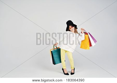 Little girl is wearing oversized hat and shoes. She is posing with colorful bags. Girl is Imitating adult woman. Shopping, purchases, buy, sale concept