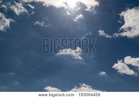 Beautiful deep blue sky with white Cumulus clouds. At the top the sun shines. From the sun in different directions the rays of the sun. Present and Cirrus clouds.