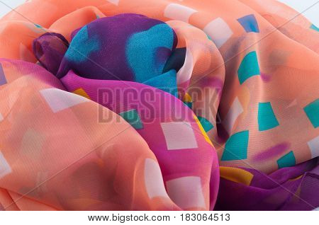 Multicolored pink yellow blue purple white chiffon fabric with different squares lay in heap