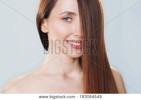 Beautiful model girl with shiny brown straight long hair . Care and hair products. Grey background