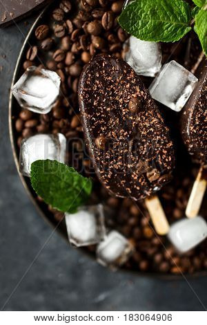 Chocolate ice cream on a stick on a gray background. Chocolate dessert. Ice. Coffee beans and chocolate. Fresh mint