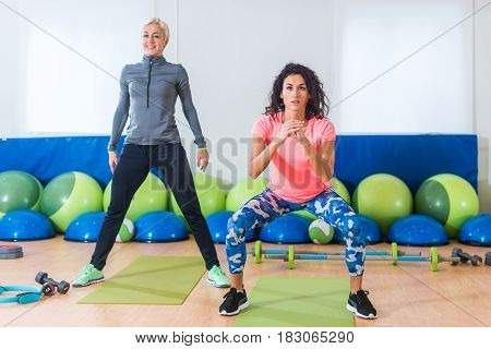 Two slim attractive sportswomen doing squat exercises during fitness class against bright equipment in gym.