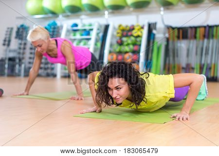 Two women doing push-ups on mats exercising in a gym.