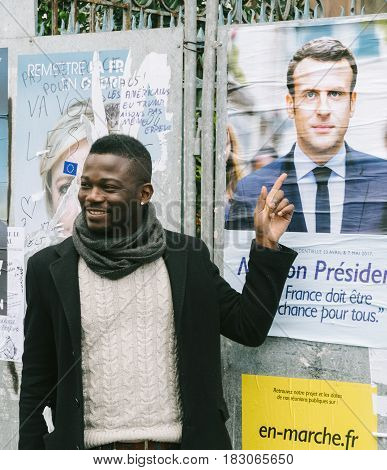 STRASBOURG FRANCE - APR 23 2017: Black ethnicity man showing his support to Emmanuel Macron near all 11 presidential posters