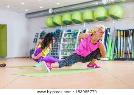 Muscular female fitness women doing stretching exercise indoors in sports club.