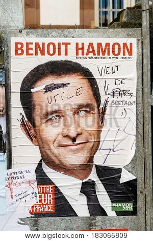 STRASBOURG FRANCE - APR 23 2017: Official campaign posters of Benoit Hamon political party leader of Parti socialiste (PS) vandalized on the first round of 2017 French presidential election