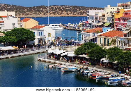 AGHIOS NIKOLAOS, CRETE, GREECE - AUGUST 2016: Small harbor with moored fishing boats at Aghios Nikolaos town on Crete island, Greece