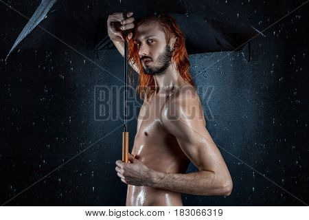 Erotic wet man under the drops of water.