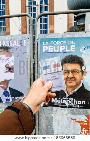 STRASBOURG FRANCE - APR 23 2017: French voter registration card held by male hand in front of official campaign poster of Jean-Luc Melenchon candidate for the 2017 French presidential elections posted outside a polling station