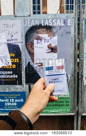 STRASBOURG FRANCE - APR 23 2017: French voter registration card held by male hand in front of official campaign poster of Jean Lassalle candidate for the 2017 French presidential elections posted outside a polling station